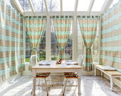 Bright sun room with dining table set — Stock Photo