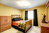 Bright yellow bedroom with carved wood furniture — ストック写真