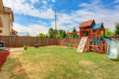 Fenced backyard with playground for kids — Stock Photo