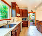 Bright kitchen with carved wood cabinets — Stock Photo