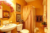 Bright luxury bathroom in gold color — Stock Photo