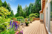 Wooden walkout deck with vibrant color flowers — Stock Photo