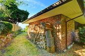 Brick house with firewoods — Stockfoto