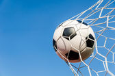 Soccer football in Goal net with the sky field. — Stock Photo