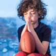 Young Hispanic child praying so the weather improves and he can go to play outdoors - Stock Photo