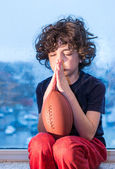 Young Hispanic child praying so the weather improves and he can go to play outdoors — Foto Stock