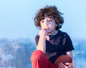 Sad child sitting on a window on a rainy day — Stock Photo