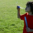 Hispanic Child Blowing Bubbles Outdoors — Stock Video