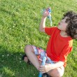 Young Boy Enjoying Blowing Soap Bubbles Outdoors — Stock Photo #30361459