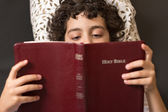Young child reading the bible in bed. Boy laying of the floor and reading the Holy Bible. The word of god being read by a small kid — Foto Stock