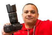 Uomo latino tenendo una fotocamera. fotografo professionista indossa un maglione rosso e tenere una macchina fotografica — Foto Stock