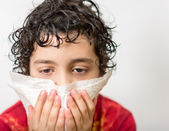 Hispanic child blowing his nose. Boy with a runny nose. Dust allergy. Kid suffering from a cold. — Foto Stock