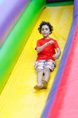 Child sliding in an inflatable playground — Stock Photo