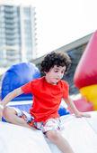 Niño jugando en el patio de juegos inflable — Foto de Stock
