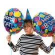 Child holding balloons during his birthday party. Boy doing funny facial expressions over white background. — Stockfoto