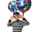 Child holding balloons during his birthday party. Boy doing funny facial expressions over white background. — Stock Photo