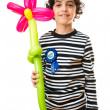 Child Holding a Flower Balloon During his Birthday party. Over white background and smiling. — Stockfoto