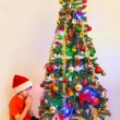 Child praying in front of a Chrismas Tree — Stock Photo