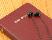 The word of God or Bible for the visually impared or totally blind. Earbuds over a bible — Stock Photo