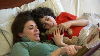 Single mother and son looking family photos in bed — Vídeo de stock