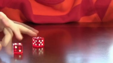 Child playing with a pair of rigged dices over a table — Stock Video