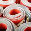 Stock Photo: Rolled magazines background