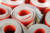 Rolled magazines background — Stockfoto