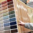 Woman choosing colorful carpet sample — Stock Photo