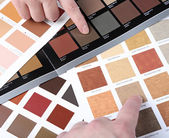 Hands pointing to sample color chart — Stock Photo