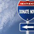 Donate now road sign — Stock Photo