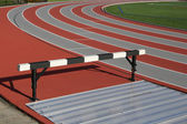 Track and athlete hurdling field — Stock Photo