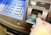 Woman insert card to withdraw money — Stock Photo