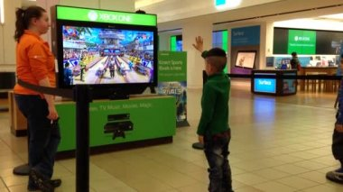 Microsoft staff demonstrates with children playing Xbox game — Stock Video