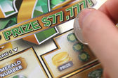 Macro woman scratching lottery ticket at prize area — Stock Photo