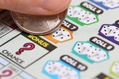 Woman scratching lottery ticket on bonus. — Stock Photo
