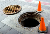 Manhole on the footbath near street — Stockfoto