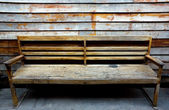Old brown bench with old wall — Stock Photo