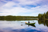 Fisherman sails on a green boat on the lake — Stock Photo
