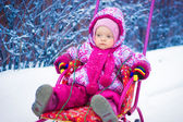 Small child is riding on a sled in the winter — Stock Photo