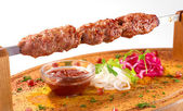 Shish kebab on a wooden stand — Stock Photo