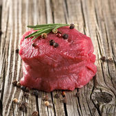 Raw steak with pepper on wood — Stock Photo