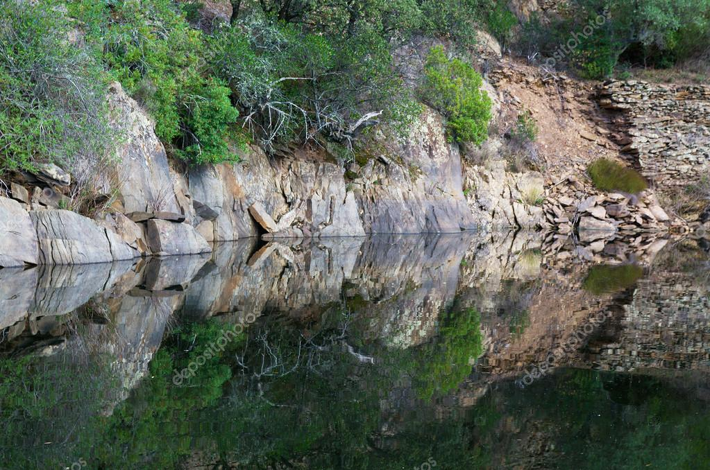 Mirror water reflection of riverbank rocks. — Stock Photo #16340341