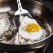 Eggs cooked with bacon grease in pan — Stock Photo #12559645