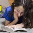 Young Girl Reading Book in Bedroom — Stock Photo #12723464