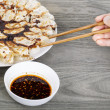 Hand held chopsticks reaching for Chinese Dumplings — Stock Photo