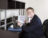 Mature Man Biting Income Tax Papers — Stock Photo