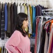 Mature woman looking at clothing while in the her walk-in closet — Stock Photo