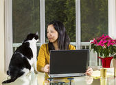 Mature woman working at home wth family looking at her — Stock Photo