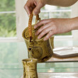 Stock Photo: Female hands pouring teinto cup