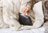 Female hand turning off alarm clock while in bed — Stock Photo